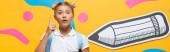 horizontální oříznutí šokovaného zorničky ukazující prstem při pohledu na kameru poblíž papírové tužky a dekorativních prvků na žluté