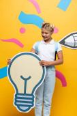 fröhliches Schulkind mit leichter Blasenmaquette auf gelbem Hintergrund mit bunten Elementen und Bleistift