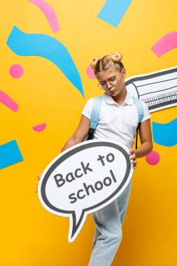 Discouraged schoolgirl holding speech bubble with back to school lettering near colorful paper elements and pencil on yellow stock vector
