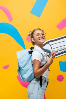 Joyful schoolgirl with backpack looking away near paper pencil and colorful elements on yellow stock vector