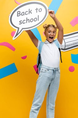 Excited schoolgirl screaming while holding speech bubble with back to school inscription near paper art and pencil on yellow stock vector