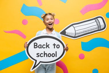 Excited schoolchild holding speech bubble with back to school lettering near multicolored paper elements and pencil on yellow stock vector