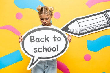 Displeased schoolgirl holding speech bubble with back to school inscription near paper pencil and decorative elements on yellow stock vector