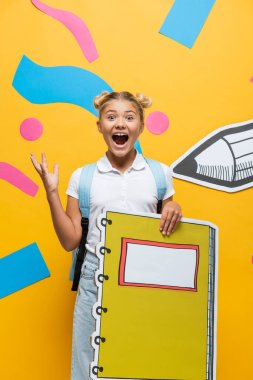 Excited schoolgirl with notebook maquette screaming and gesturing on yellow background with decorative elements and paper cut pencil stock vector