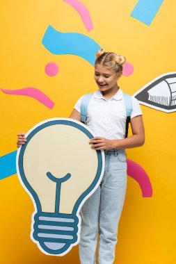 Joyful schoolchild holding light bubble maquette on yellow background with colorful elements and paper cut pencil stock vector