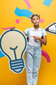 Schoolgirl with backpack pointing with finger at decorative light bulb near paper art on yellow background