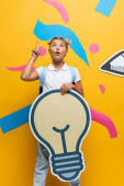 Photo Pensive schoolgirl having idea while holding decorative light bulb near paper art on yellow background