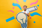 Schoolkid looking at camera while holding paper light bulb near paper art on yellow background