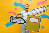 Nadšený školák drží papírové tužky a notebook na žlutém pozadí