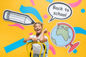 Schoolkid holding book and apple near paper speech bubble and artwork on yellow background