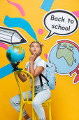 Pensive child holding globe near speech bubble with back to school lettering and paper art on yellow background