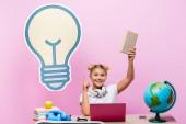 Kid ukazuje prstem, zatímco drží knihu v blízkosti zeměkoule, gadgets a papírové kresby na růžovém pozadí