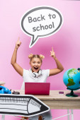 Izgalmas gyerek rámutatva beszéd buborék vissza az iskolába felirat közelében laptop, okostelefon és gömb az asztalon rózsaszín háttér