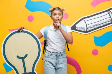 Schoolgirl showing quiet gesture while holding decorative light bulb near paper art on yellow background stock vector