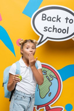 Shocked schoolkid holding apple and covering mouth near speech bubble with back to school lettering on yellow background stock vector