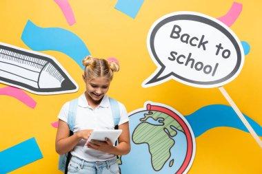 Okul çocuğu konuşma balonunun yanında dijital tablet kullanıyor okula geri dönüyor ve sarı arka planda kağıt resimleri var.