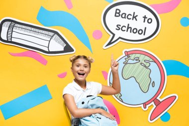Schoolchild with backpack pointing at back to school lettering and paper elements on yellow background stock vector