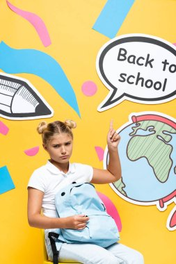 Sad schoolgirl with backpack pointing at speech bubble with back to school lettering and paper art on yellow background stock vector