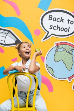 Excited kid with apple and book looking at speech bubble with back to school lettering and paper art on yellow background stock vector