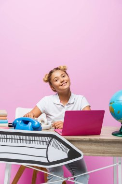 Child sitting near laptop, globe and paper art on desk on pink background stock vector