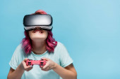 KYIV, UKRAINE - JULY 29, 2020: concentrated young woman with pink hair in vr headset playing video game with joystick isolated on blue