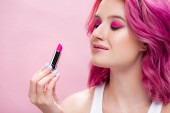 young woman with colorful hair holding lipstick isolated on pink