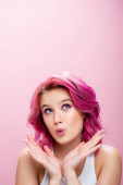 Photo surprised young woman with colorful hair and makeup posing with hands near face isolated on pink