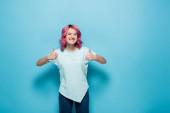 mladá žena s růžovými vlasy ukazující palce nahoru na modrém pozadí
