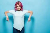 fiatal nő rózsaszín haj mutatva le a kék háttér
