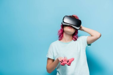 KYIV, UKRAINE - JULY 29, 2020: young woman with pink hair in vr headset with joystick on blue background stock vector