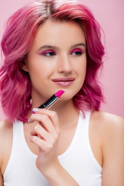 Young woman with colorful hair holding lipstick isolated on pink stock vector