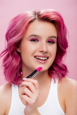 Young woman with colorful hair holding lipstick and smiling isolated on pink stock vector