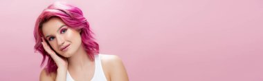 Young woman with colorful hair and makeup touching face isolated on pink, panoramic shot stock vector