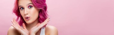 Surprised young woman with colorful hair and makeup posing with hands near face isolated on pink, panoramic shot stock vector