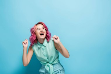 Young woman with pink hair rejoicing on blue background stock vector