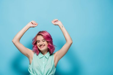Young woman with pink hair and hands in air smiling on blue background stock vector