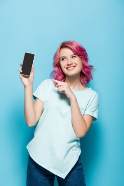 Young woman with pink hair pointing at smartphone with blank screen on blue background stock vector