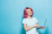 mladá žena s růžovými vlasy pomocí notebooku na modrém pozadí