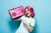 excited young woman with pink hair pointing at vintage tape recorder on blue background