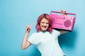 mladá žena s růžovými vlasy drží vinobraní magnetofon a ukazuje rock znamení na modrém pozadí