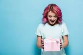 vzrušená mladá žena s růžovými vlasy držení dárkové krabice s lukem na modrém pozadí
