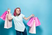 fiatal nő rózsaszín haj gazdaság bevásárló táskák és mosolygós kék háttér