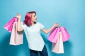 mladá žena s růžovými vlasy drží nákupní tašky na modrém pozadí