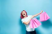 šokovaná mladá žena s růžovými vlasy drží nákupní tašky na modrém pozadí