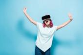 izgatott fiatal nő rózsaszín haj vr headset kezek levegőben kék háttér
