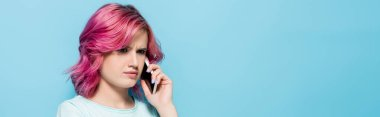 Confused young woman with pink hair talking on smartphone on blue background, panoramic shot stock vector