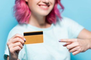 Selective focus of young woman with pink hair pointing at credit card on blue background stock vector