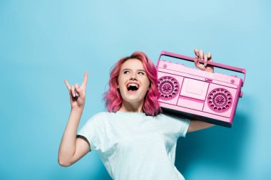 Excited young woman with pink hair holding vintage tape recorder and showing rock sign on blue background stock vector
