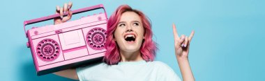 Excited young woman with pink hair holding vintage tape recorder and showing rock sign on blue background, panoramic shot stock vector