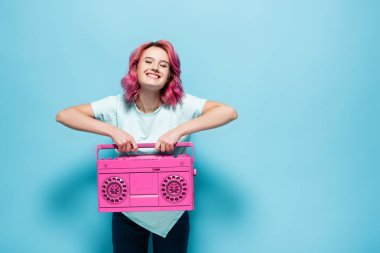Young woman with pink hair holding vintage tape recorder on blue background stock vector
